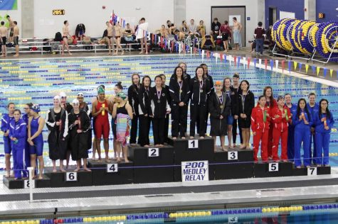 The LRHS Girls Swim Team takes their place on the podium.