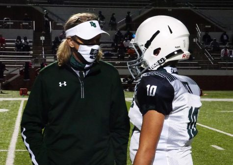 Football coach Shawn Alsup talks with one of his players during a game Oct. 13. Players and coaches have to wear masks during a game.